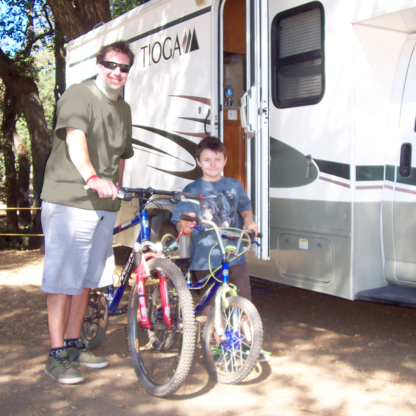 Father and son with bikes in front of an RV